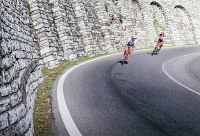 Photograph - Two High-speed Cyclists Ride Downhill On A Curve In Como, Italy by Alexandre Rotenberg