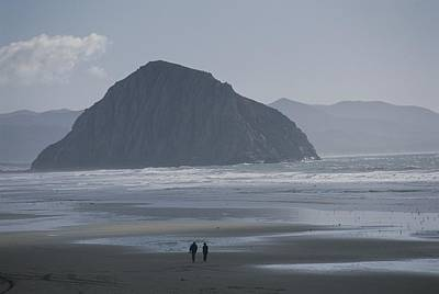 Beach Scenes Photograph - Two People Walk Along A Beach by Marc Moritsch