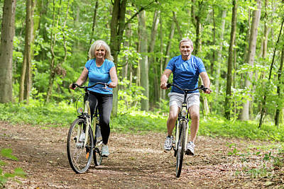 Photograph - Two Senior People Cycling In The Woods. by Michal Bednarek