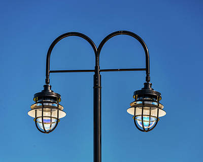 Photograph - Two Streetlamps Against A Blue Sky by Gary Slawsky