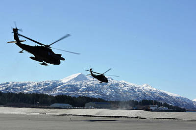 Photograph - Two Us Army Black Hawk Helicopters Launch Towards Villages On Kodiak Island by Paul Fearn