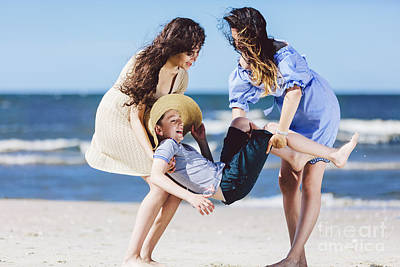 Photograph - Two Women Carrying A Boy In A Straw Hat On The Beach. by Michal Bednarek