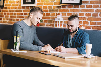 Photograph - Two Young Men Sitting In A Cafe, Discussing. by Michal Bednarek