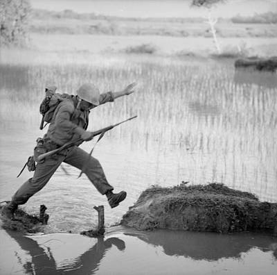 Cold War Era Photograph - Vietnam War. A Us Marine Rifleman Leaps by Everett