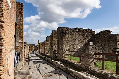 Photograph - Walking Around Ancient Pompeii - Long Street With A Lone Tourist by Georgia Mizuleva