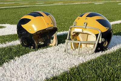 Photograph - Wolverine Helmets From Different Eras On The Field by Michigan Helmet