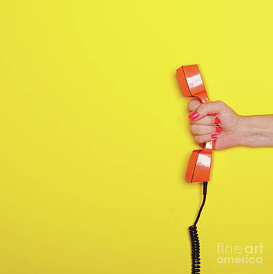 Pop Photograph - Woman Hand Holding Retro Orange Phone Tube Against Yellow Backgr by Aleksandar Mijatovic