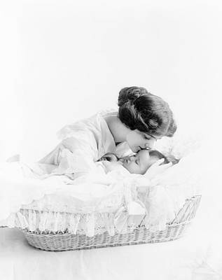 Bassinet Photograph - Woman Kissing Baby In Bassinet by Bill Cannon
