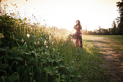 Woman Standing Among Wildflowers In Meadow At Sunset Art Print by Bradley Hebdon