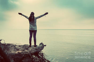 Cloudy Photograph - Woman Standing On Broken Tree On Wild Beach With Arms Raised Looking At Sea by Michal Bednarek