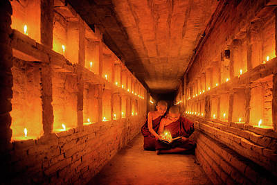 Small Statue Photograph - Young Buddhist Monk Are Reading A Book With Light From Candle  by Anek Suwannaphoom