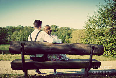 Winter Animals - Young couple in love sitting on a bench in park by Michal Bednarek