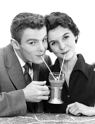Photograph - Young Couple Sharing A Milkshake by H. Armstrong Roberts/ClassicStock