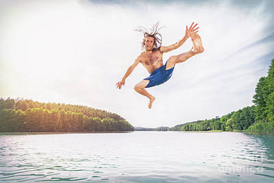 Outdoor Photograph - Young Fit Man Making A Jump Into A Lake. by Michal Bednarek