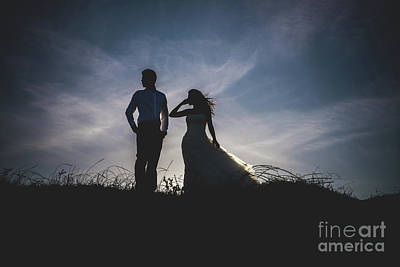 Latidude Image - Bride and groom backlit in a sunset on the beach. by Joaquin Corbalan