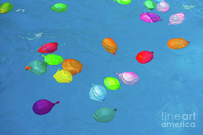 Going Green - Colorful plastic water balloons floating in a pool to play on va by Joaquin Corbalan