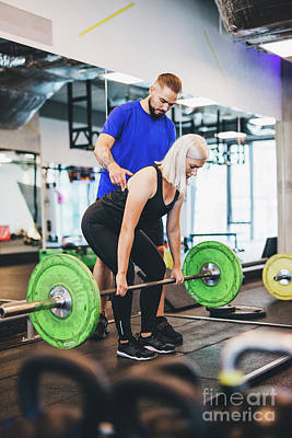 Travel - Personal trainer assisting woman lifting weights. by Michal Bednarek