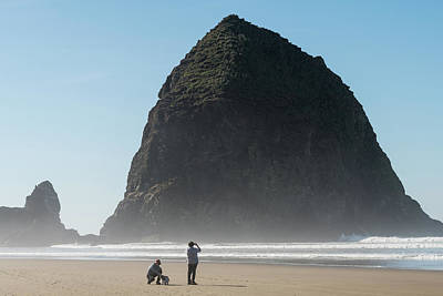 Scifi Portrait Collection - Tourists with a dog  enjoying the beach with Haystack Rock in thCANNON BEACH, OREGON, USA - October  by Esteban Martinena Guerrero