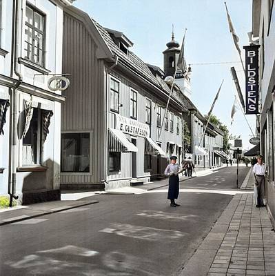 Vermeer Rights Managed Images - A boy standing in Norra Storgatan  North High Street  with shops. In the background the tower of Ek Royalty-Free Image by Ahmet Asar