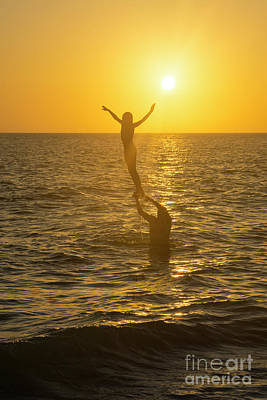 Photograph - A Father Lifts His Daughter Out Of The Water Along The Beach At  by William Kuta
