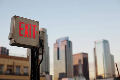 Photograph - An Exit Sign In Fron Of A Big City by Frank Rothe