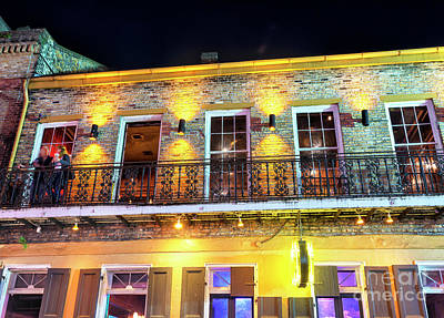 Photograph - Balcony Couple At Night In New Orleans by John Rizzuto