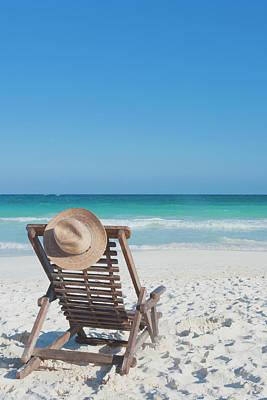 Lounge Chair Photograph - Beach Chair With A Hat On An Empty Beach by Sasha Weleber