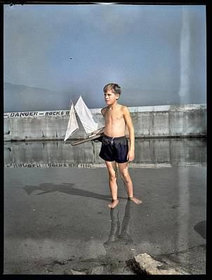 Painting Royalty Free Images - Boy with toy sailboat at the beach on the last day of summer 1952  Royalty-Free Image by Artistic Panda
