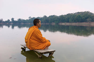 Photograph - Buddhist Monk Sitting On Waters Edge by Martin Puddy