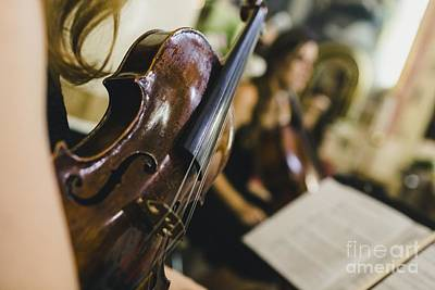 Music Royalty-Free and Rights-Managed Images - Classical musicians hold their musical instrument, a violin, whi by Joaquin Corbalan