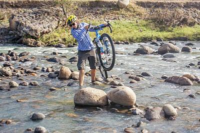 City Scenes - Cyclist crossing Rio Humuya in Honduras. by Marek Poplawski