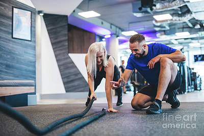 Photograph - Gym Instructor And A Woman Exercising At The Gym. by Michal Bednarek