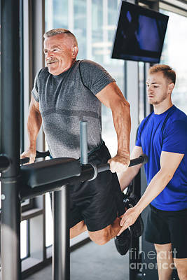 Photograph - Gym Instructor Helping Senior Man At The Gym. by Michal Bednarek