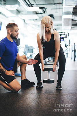 Photograph - Gym Trainer Assisting The Exercising Woman. by Michal Bednarek