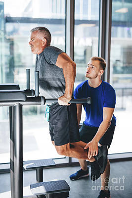 Photograph - Man Helping Senior Man With His Workout At A Gym. by Michal Bednarek