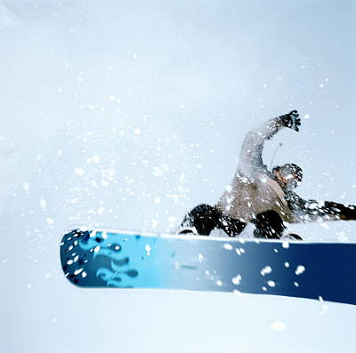 Photograph - Man Snowboarding, Mid-jump. Low Angle by Martin Barraud