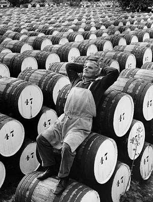 Hand Photograph - Mature Man Relaxing On Barrels B&w by Hulton Archive