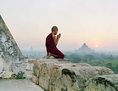 Sunlight Photograph - Myanmar, Bagan, Buddhist Monk Praying by Martin Puddy