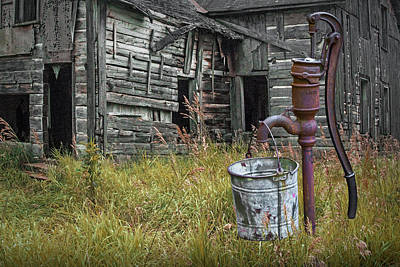 Photograph - Old Water Pump With Metal Bucket By An Old Weathered Abandoned F by Randall Nyhof