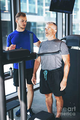 Photograph - Personal Trainer Giving Instructions To Older Man At The Gym by Michal Bednarek