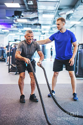 Photograph - Senior Man Exercising At The Gym With Gym Instructor. by Michal Bednarek