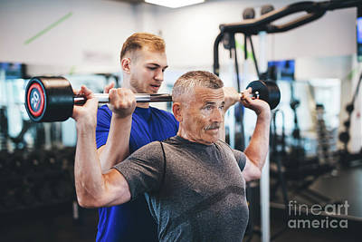 Photograph - Senior Man Lifting Weights With Help Of Gym Assistant. by Michal Bednarek