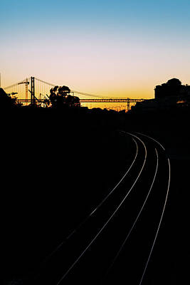 Photograph - Silhouette Of A Backlit 25 April Bridge In Lisbon, Portugal At Sunset With Train Tracks On Foreground. by Alexandre Rotenberg