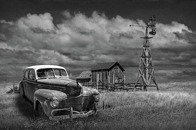 Randall Nyhof Royalty Free Images - Vintage Automobile and Wooden Barn with Windmill in Black and White Royalty-Free Image by Randall Nyhof
