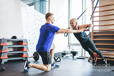 Photograph - Woman Exercising With Personal Trainer At The Gym. by Michal Bednarek