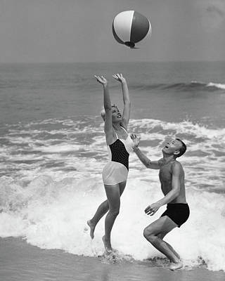 Couple Photograph - Young Couple Playing With Beach Ball At by Stockbyte
