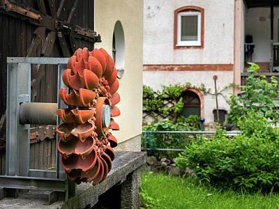 Photograph - An old orange Pelton wheel hanging outside by Stefan Rotter
