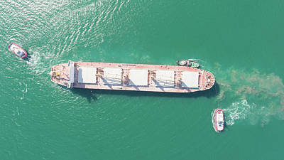 Truck Art Rights Managed Images - Aerial top down view of Tug boats assisting big cargo ship. Large cargo ship enters the port escorted by tugboats. Royalty-Free Image by Michael Dechev