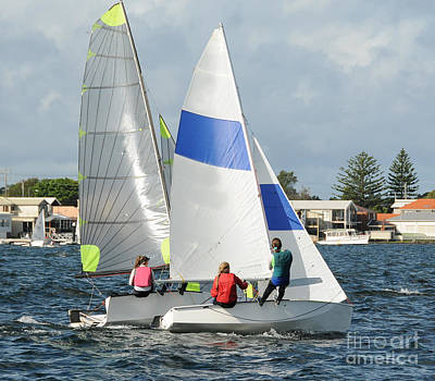 A White Christmas Cityscape - Children close racing small sailboats  on a coastal lake. by Geoff Childs