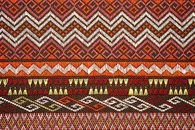 Curated Travel Chargers - More than 100 years old colorful thai handcraft peruvian style rug surface old vintage torn conservation Made from natural materials Chemical free close up.  by Julien